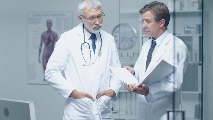 Two Specialist Doctors Discussing Patient's Log. Both are Senior and Experienced. Their Office Looks Modern and Respectable. Shot on RED Cinema Camera in 4K (UHD). | Shutterstock HD Video #22782499