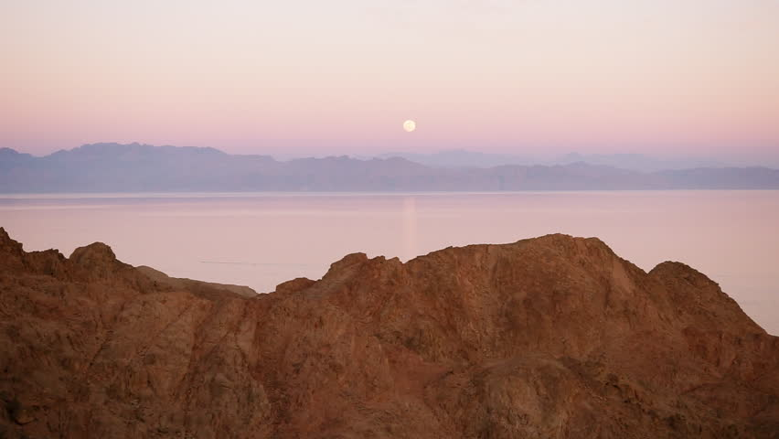 The full moon rises from beyond the mountains of Saudi Arabia above the sea in the Gulf of Aqaba . Egypt.