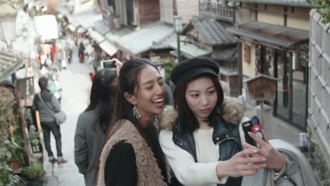International friends take selfie in Kyoto old street. Two friends take photos on Famous Japanese Street in Kyoto.