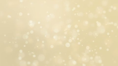 Beautiful soft golden background with moving light particles creating a bokeh effect.