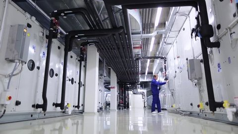 A man checks heating and ventilation systems on the technical floor at an industrial or office building