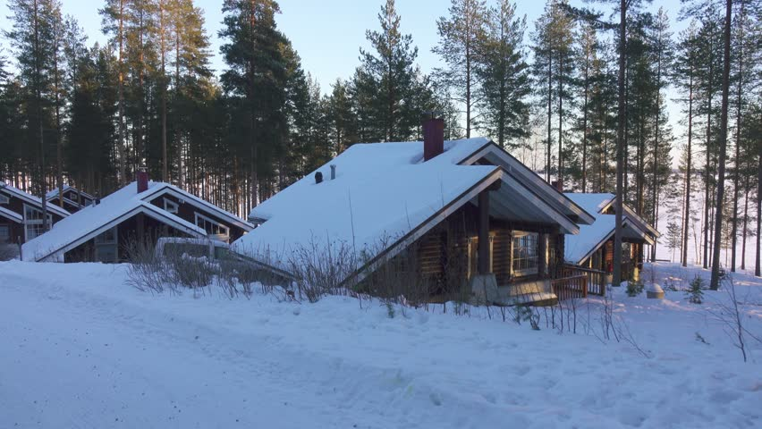 Moving at winter by cozy wooden house in snowy forest village situated on lake shore in Finland .