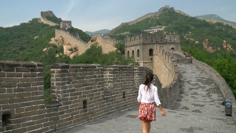 Fun happy cheerful joyful tourist woman at Great Wall of China on travel smiling laughing and dancing during vacation trip in Asia. Girl visiting and sightseeing Chinese attraction in Badaling