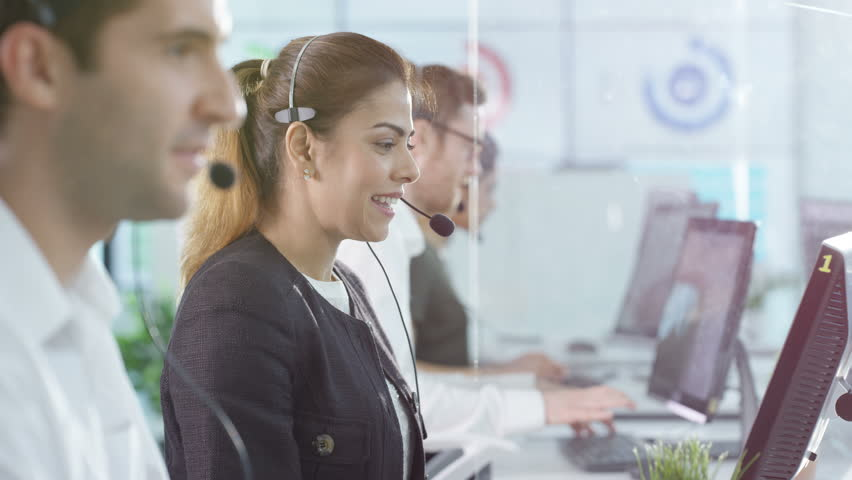 4K Portrait smiling customer service operator taking calls in busy call center Dec 2016-UK | Shutterstock HD Video #22933819