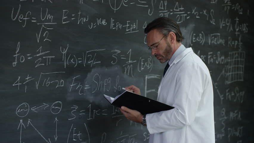 4K Portrait smiling man in white coat writing math formulas on blackboard Dec 2016-UK