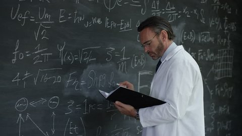 4K Portrait smiling man in white coat writing math formulas on blackboard Dec 2016-UK