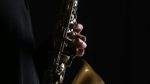 Man's fingers playing on the saxophone beautiful blues melody. Closeup