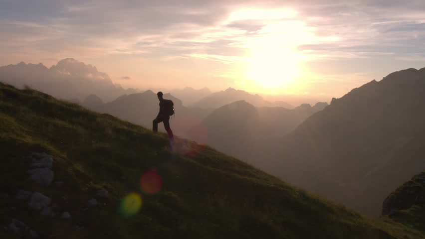 Aerial, unedited - Epic shot of a man hiking on the edge of the mountain as a silhouette in beautiful sunset