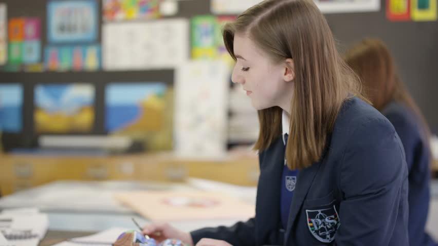 4K Teen girl working quietly on a project in school art class Dec 2016-UK