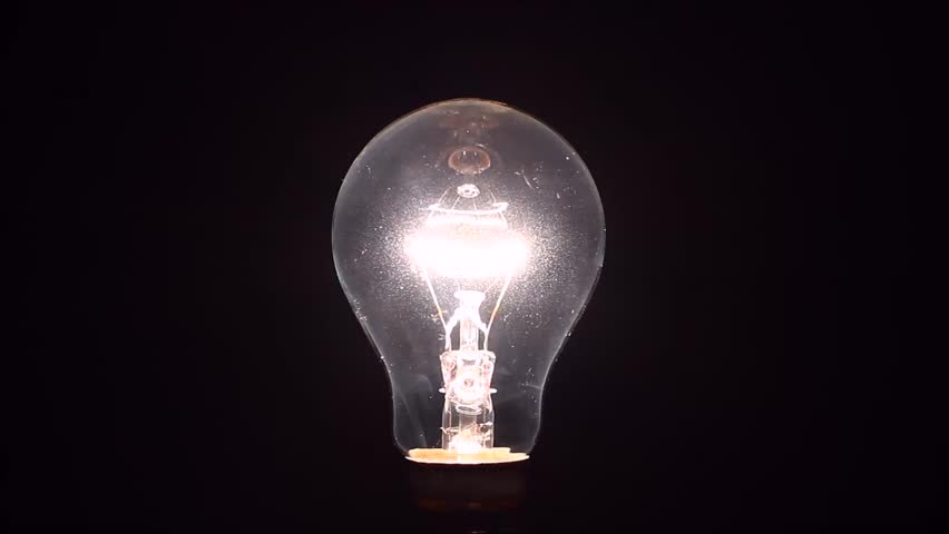 Light bulb slowly dimming isolated on a black background