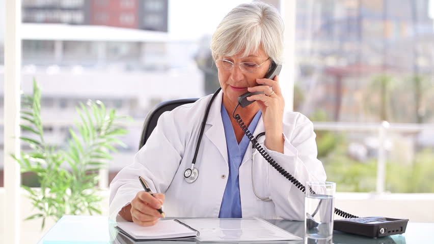 Smiling doctor talking on the phone while sitting in a bright office