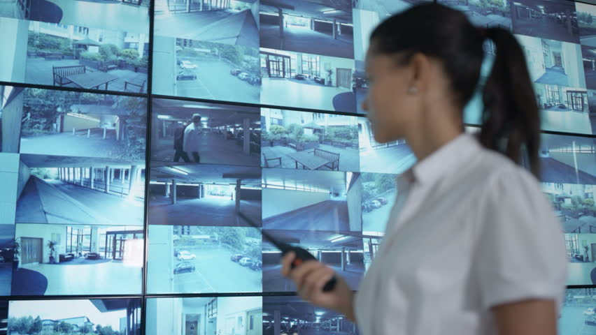 4K Security officer watching CCTV video screens & talking on radio Dec 2016-UK | Shutterstock HD Video #23015959