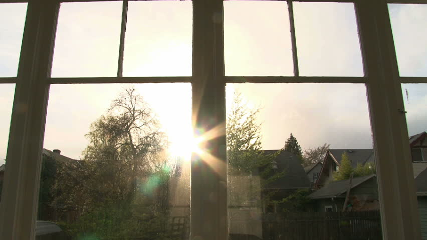 Time lapse of sunset with solar flare through house windows.
