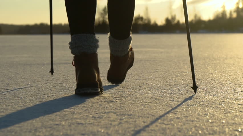 Young woman in bright red jachet and in brown boots with red laces nordic walking on frozen lake at snowly winter under sunlight. #23022739