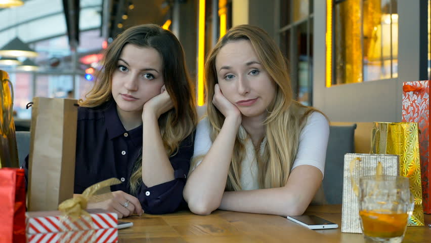 Sad girls sitting in the cafe and looking to the camera, steadycam shot