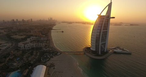 DUBAI, UAE - JANUARY 4,2017:Aerial view of Burj al Arab at sunset with The Palm on the background.The Burj al-Arab is a symbol of Dubai a luxury hotel standing on an artificial island next to Jumeirah