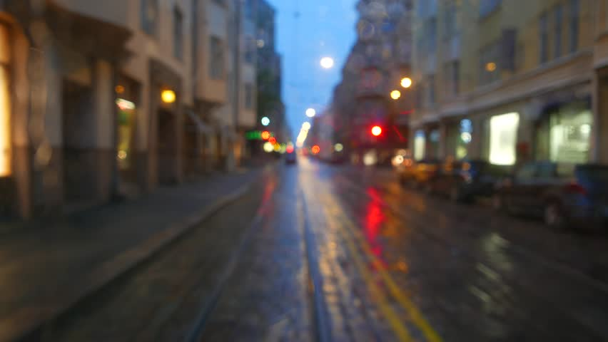 Blurred evening street wet after rain, view through rear window of moving tram vehicle, raindrops circlet on glass. Street car run then stop, nice and charming atmosphere of european city at blue hour #23060209