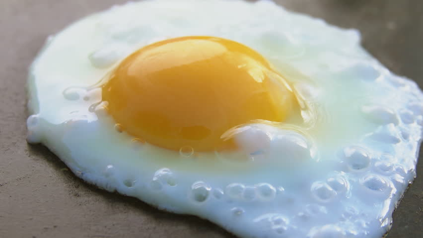 Egg fried on a hot black stone surface