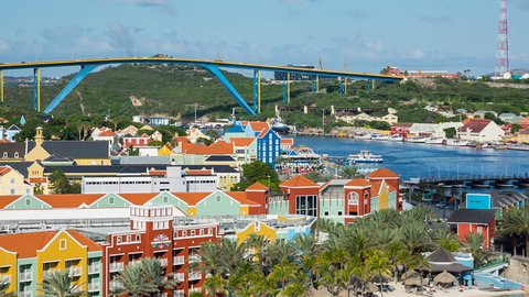 WILLEMSTAD, CURACAO - JANUARY 13, 2017: Panning across port area of the Willemstad. View of the port area with its unique architecture and harbor. Queen Juliana Bridge in the background.