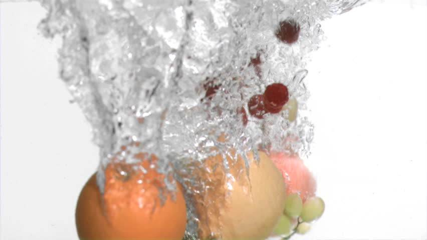 Fruits in super slow motion falling in the water against a white background