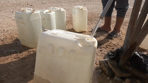 Closeup of Syrian refugees filling jerrycans with water in the Zaatari refugee camp in Jordan