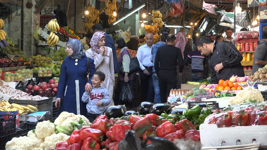 AMMAN, JORDAN - NOVEMBER 2016: Men and women do groceries at a busy fruit and vegetable bazaar in Amman, capital city of Jordan in the Middle East