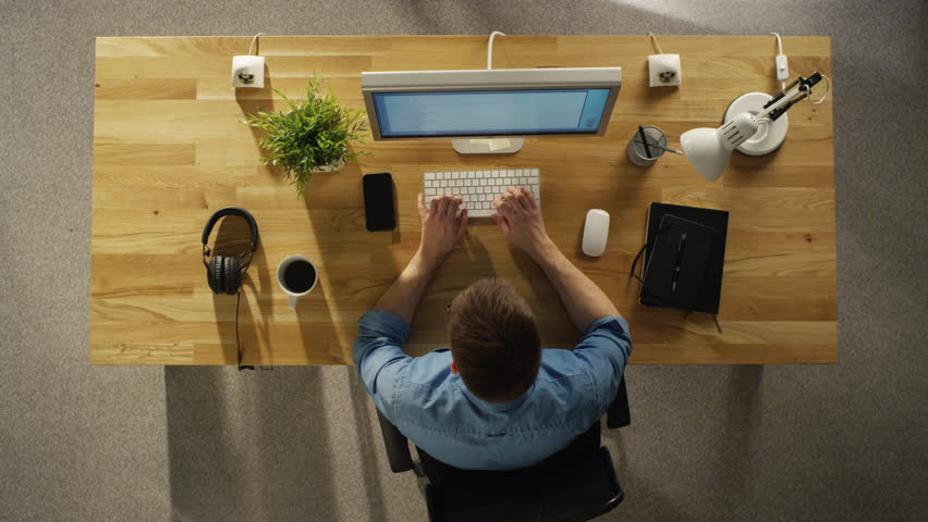 Top View of a Time-Lapse of a Whole Working Day of a Creative Designer. Working on His Desktop Computer, Drinking Coffee, Going To Lunch, Writing Down Stuff in His Notebook and Going Home.  | Shutterstock HD Video #23115982