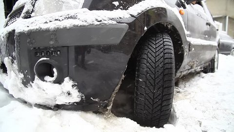 Color footage of a car's wheel being stuck in snow, and spinning.