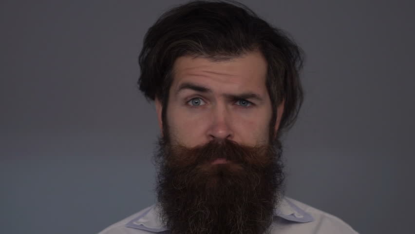 Slow motion: Surprised man raises eyebrows. Bearded man with emotional eyebrows and dark hair | Shutterstock HD Video #23141887