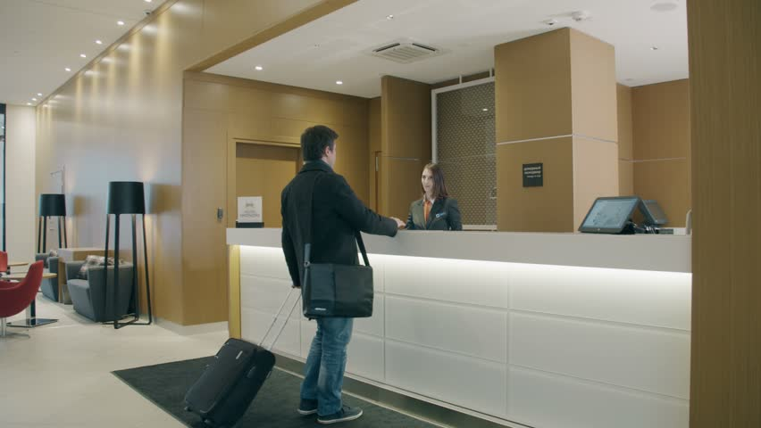 Saint-Petersburg, 15 sept. 2016. Young businessman guest with bag and suitcase arrives at the hotel and goes to the hotel reception to check-in. Lovely modern interior