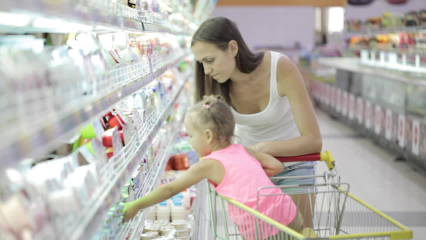 Young attractive woman with cute daughter in shopping cart choosing a yogurt in grocery section at supermarket | Shutterstock HD Video #23156275