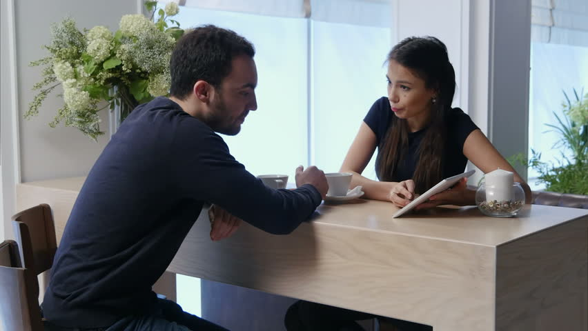 Young couple in a cafe discussing something looking at digital tablet | Shutterstock HD Video #23158909