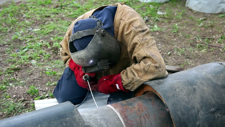 Welding an oil pipeline. Portrait of a welder with protective equipment welding outdoors. HD1080p.