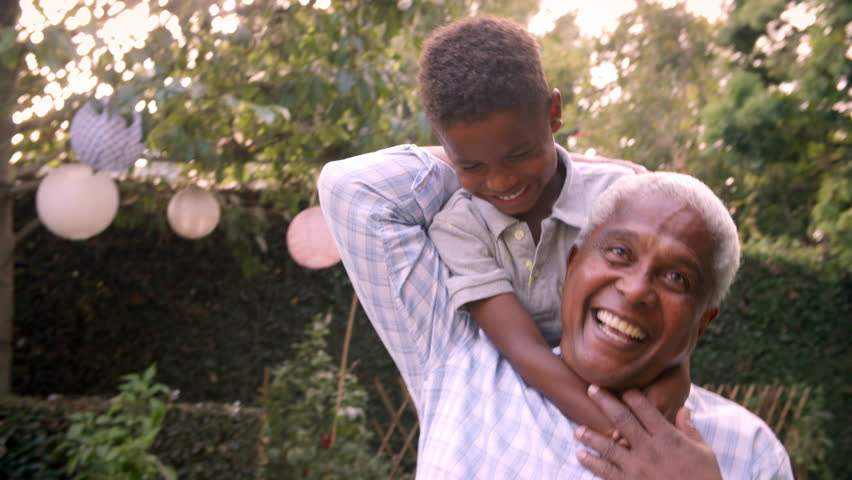Young black boy playing with grandad in the garden, close up