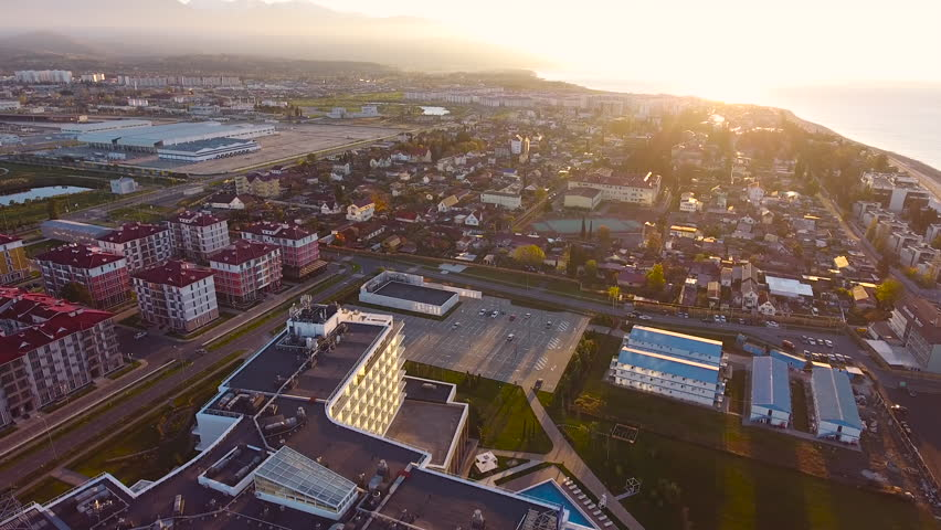 Aerial View. Flying over the city buildings houses  sea near the beach on a sunny day. Sochi Adler olympiad. Aerial drone shot. 4K 30fps ProRes (HQ) | Shutterstock HD Video #23192377