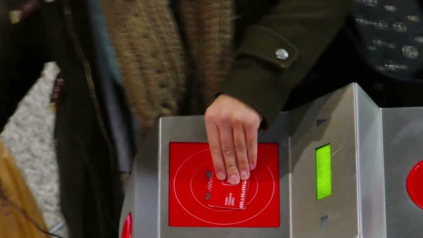passing ticket card on turnstile to get into subway underground