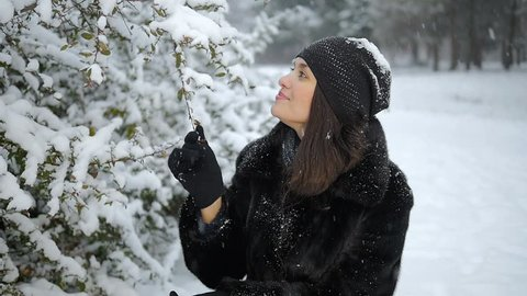 Snow falls from the branch to the girl's face. Winter park. Winter forest. Winter bushes in the snow. Touching hands snow-covered branch.