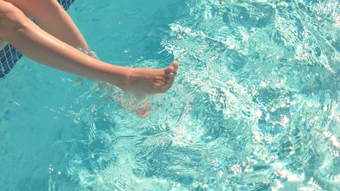Legs of woman in water. Swimming pool and sunlight. Forget troubles and enjoy vacation.