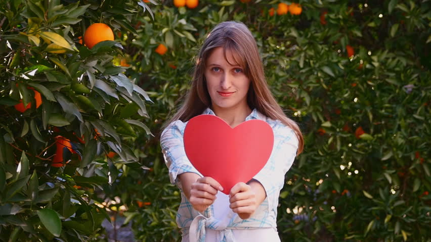 Young woman throwing her hair back with red paper heart | Shutterstock HD Video #23236498