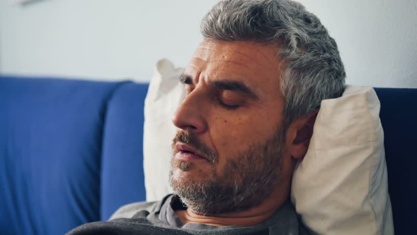 sick man on bed with breathing problems coughing using aerosol nubulizer inhaler