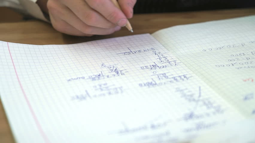 Schoolboy sitting at the school desk writes the text in the notebook indoors | Shutterstock HD Video #23248429
