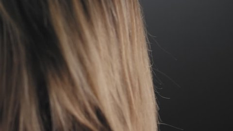 Close up shot of an athletic caucasian woman tying her hair into a ponytail on a foggy dark background