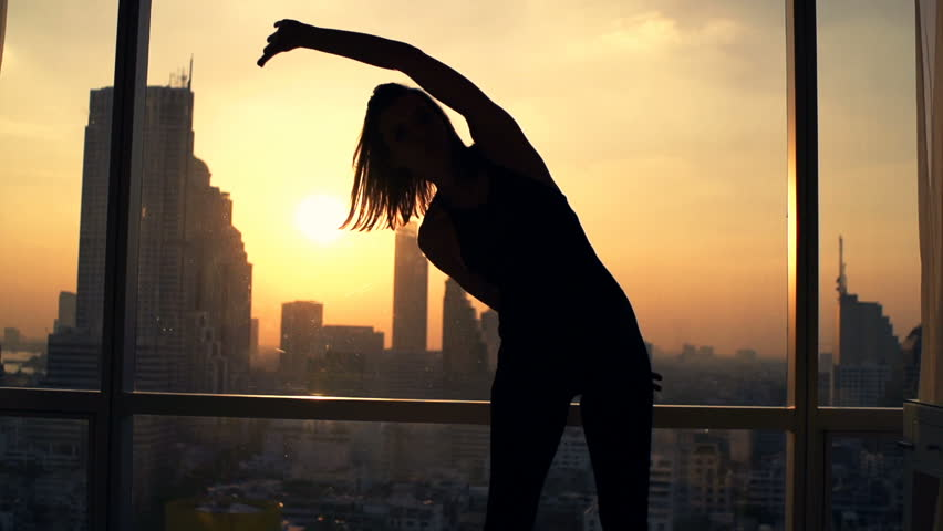 Silhouette of woman exercising bend by window during sunset at home, super slow motion 240fps