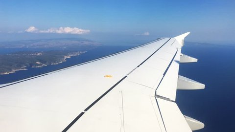 View from the plane of the passenger plane the plane wing, flaps of the plane move, below float islands, roofs of houses, the seas