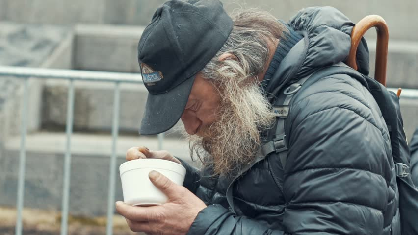 Prague, Czech Republic - December 24, 2016: Poor homeless beard eating soup plastic plates - slow motion