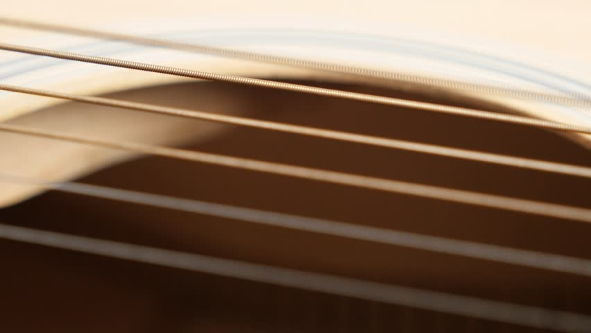 Plucked instrument body details shallow DOF 4K 2160p 30fps UltraHD panning footage - Wooden acoustic guitar E string vibration slow pan 3840X2160 UHD video