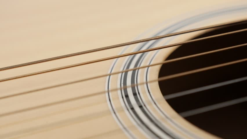 Wooden acoustic guitar playing shallow DOF slow-mo 1920X1080 HD footage - Plucking strings and vibration of instrument body slow motion 1080p FullHD video