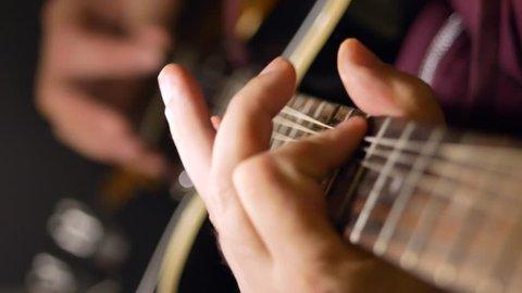 A man plays the guitar. Close-up