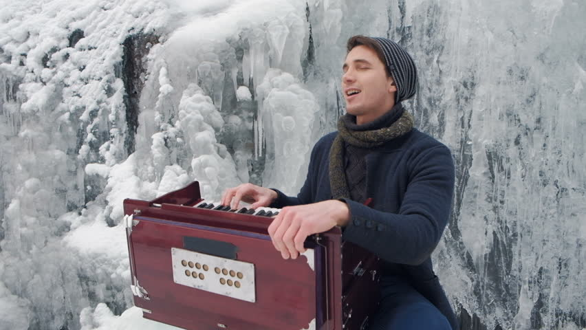 Happy young man playing the harmonium on a frozen waterfall