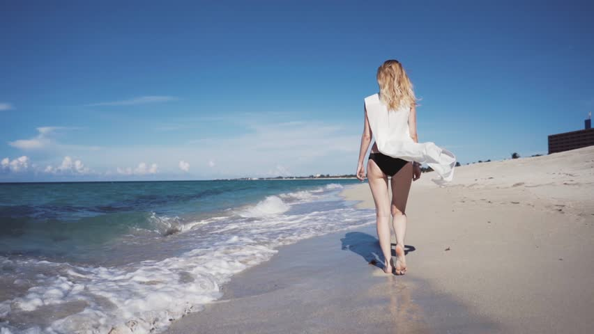 The beautiful blonde in a bikini and sunglasses walking on the beach. The wind blows and tosses her hair and snow-white cape. Beach Cuba Varadero resort. Coast Ocean. woman model walking on the beach